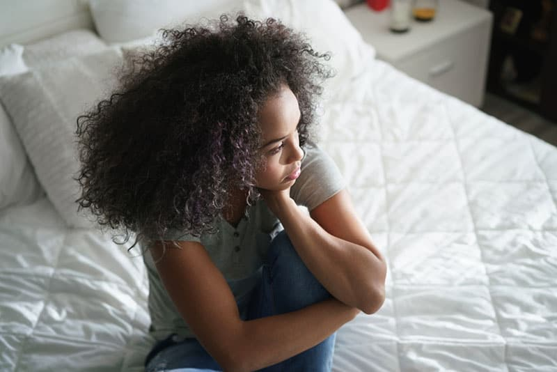 anxious woman sitting on the bed
