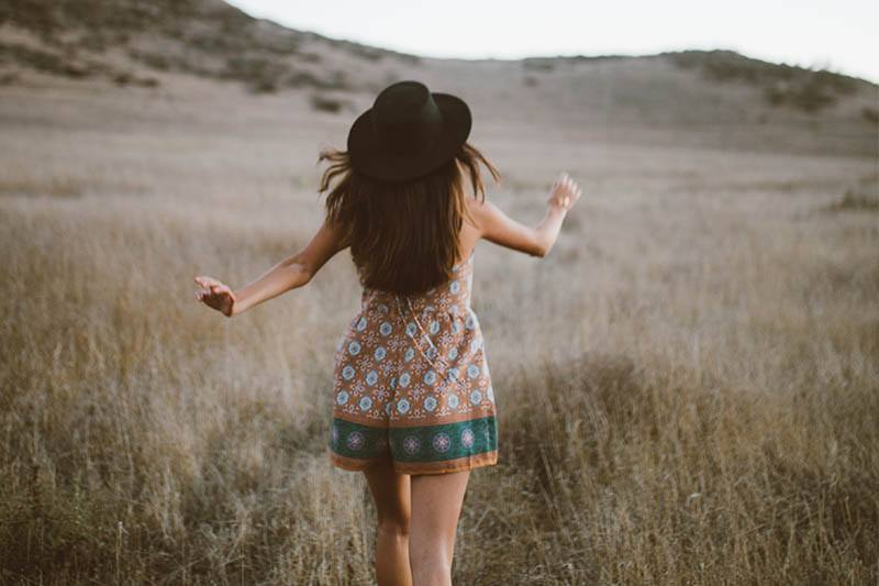 back view of girl wearing hat and walking on field