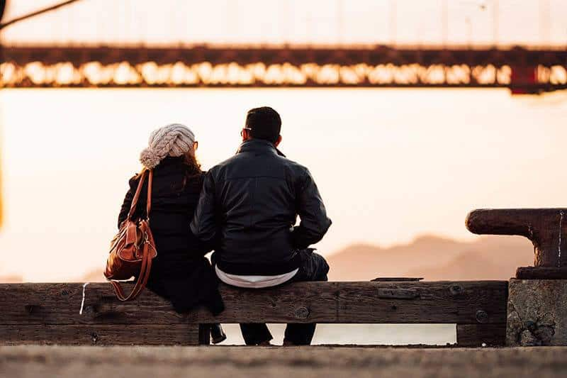 back view of male and female sitting on park bench