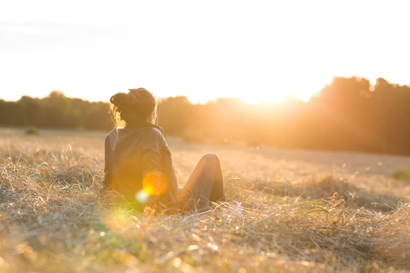 beautiful young woman on meadow watching the sunset