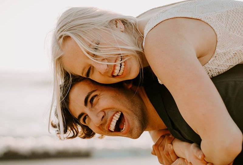 close up photo of smiling man piggybacking happy blonde woman outside