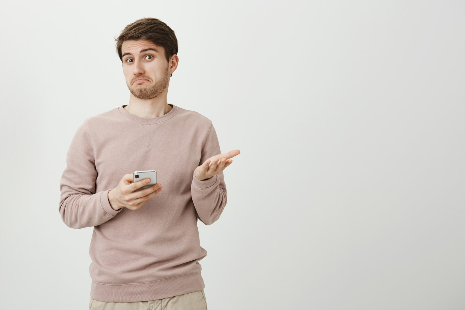 confused man looking at camera while holding a phone