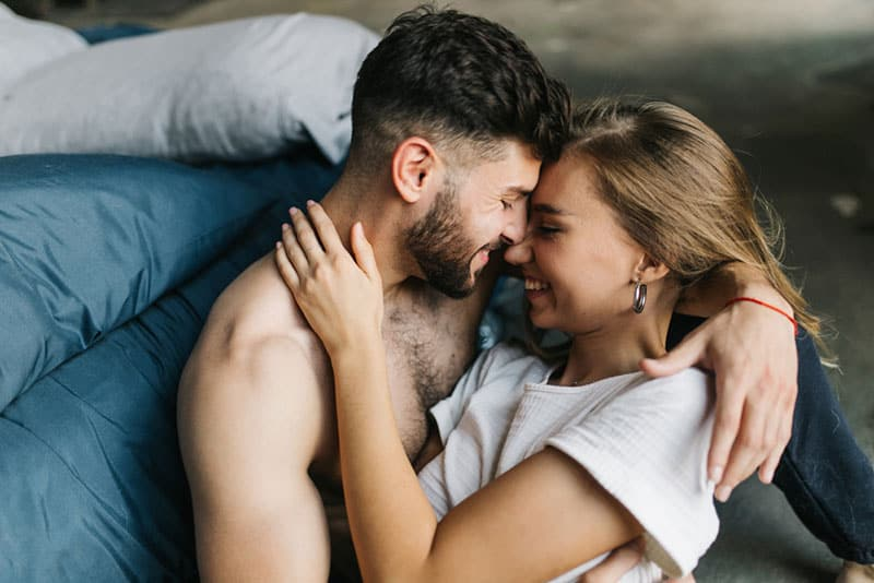 couple cuddling on the floor by the bed