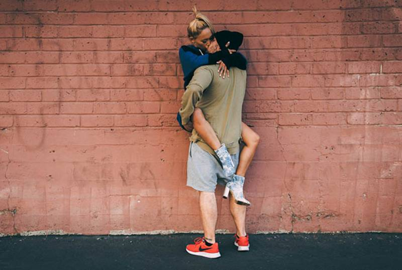 couple kisses outside in front of wall