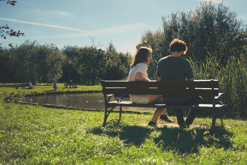 couple sitting in front of lake on a park bench