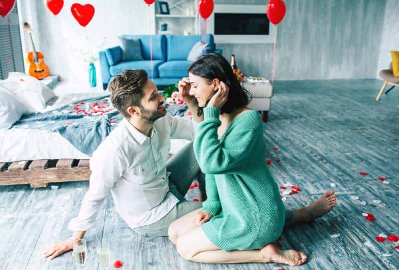 couple sitting together on the floor in romantic bedroom