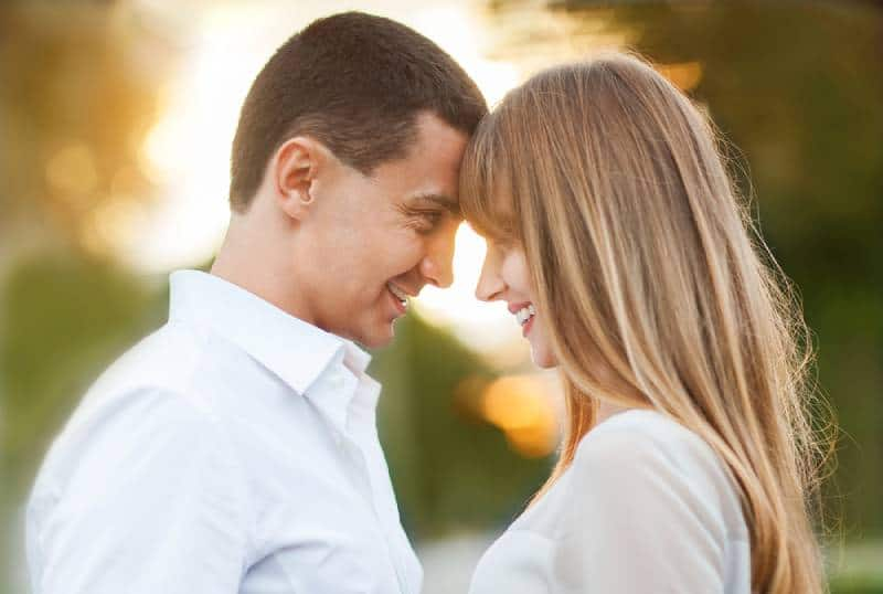 couple smiling and looking at each other outside