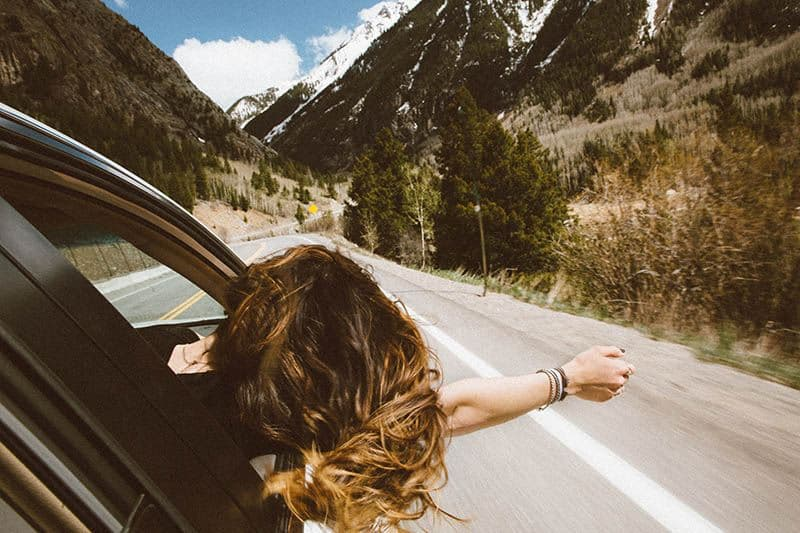 girl driving in car with head out of window