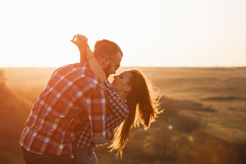 happy couple hugging at sunset