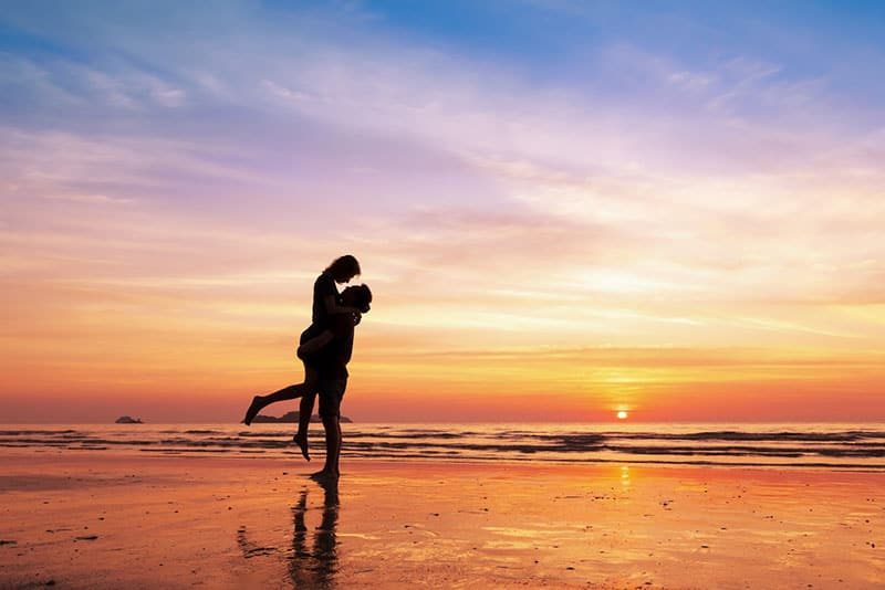 happy couple on the beach in sunset