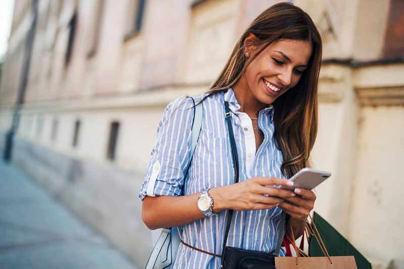 happy woman walking and texting