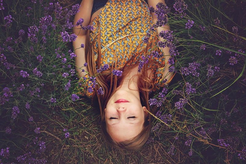 hippi young smiling girl lying on grass field