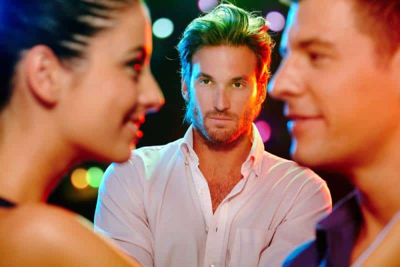 jealous man looking at man and woman o dance floor