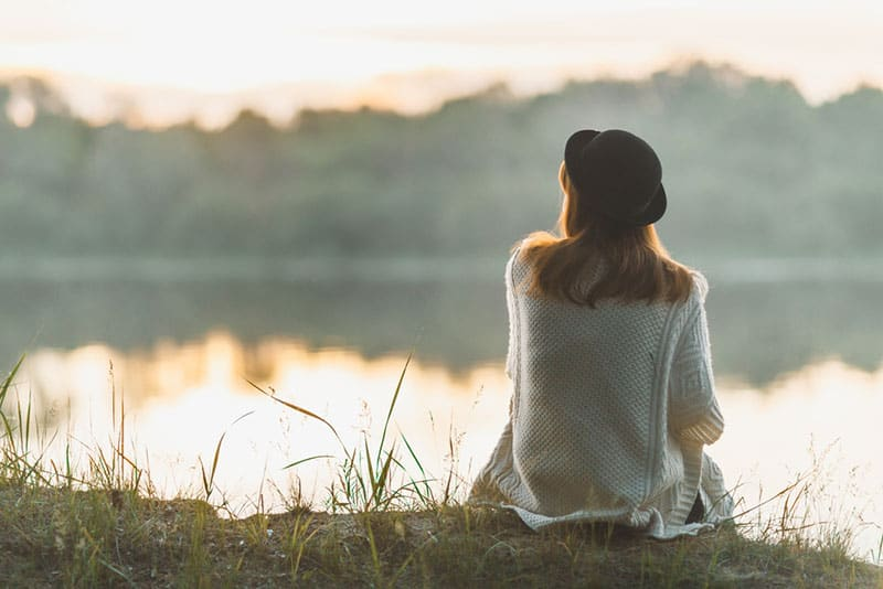 lonely woman sitting on the grass by the lake