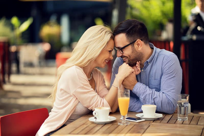 lovely couple facing each other at cafe