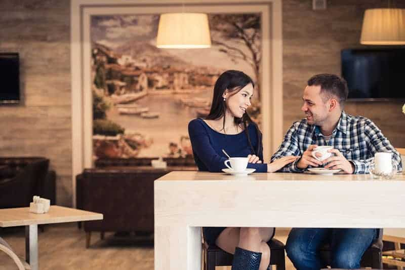 man and woman having conversation in cafe