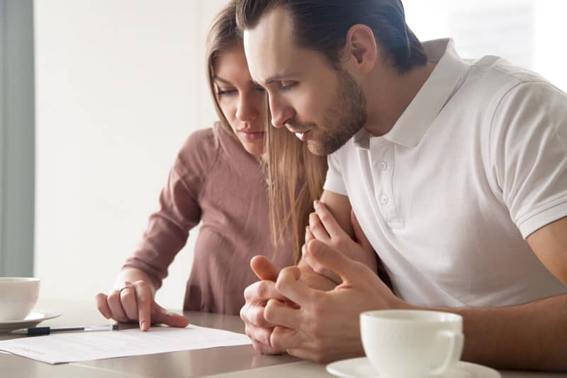man and woman looking at paper on table while sitting at home