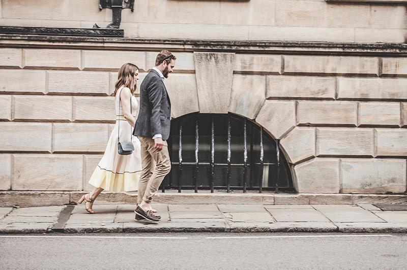 man and woman walking on sidewalk