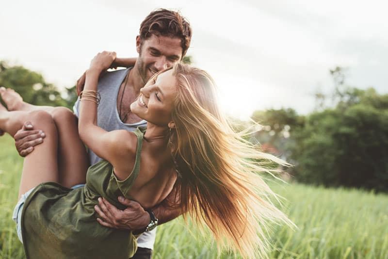 man holding a woman in the field