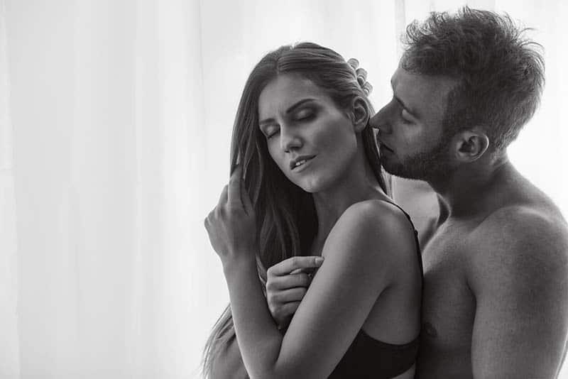man kissing a woman behind the ear