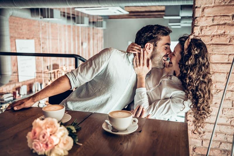 man kissing woman at cafe