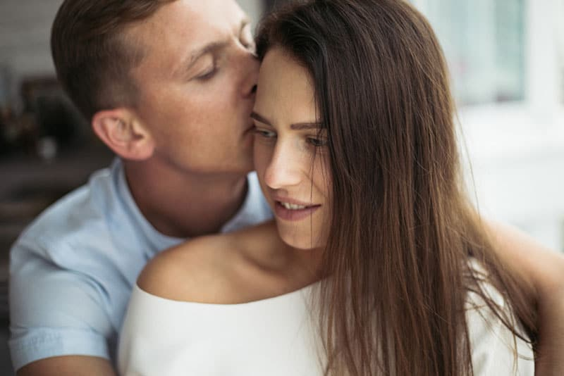 man kissing woman in head