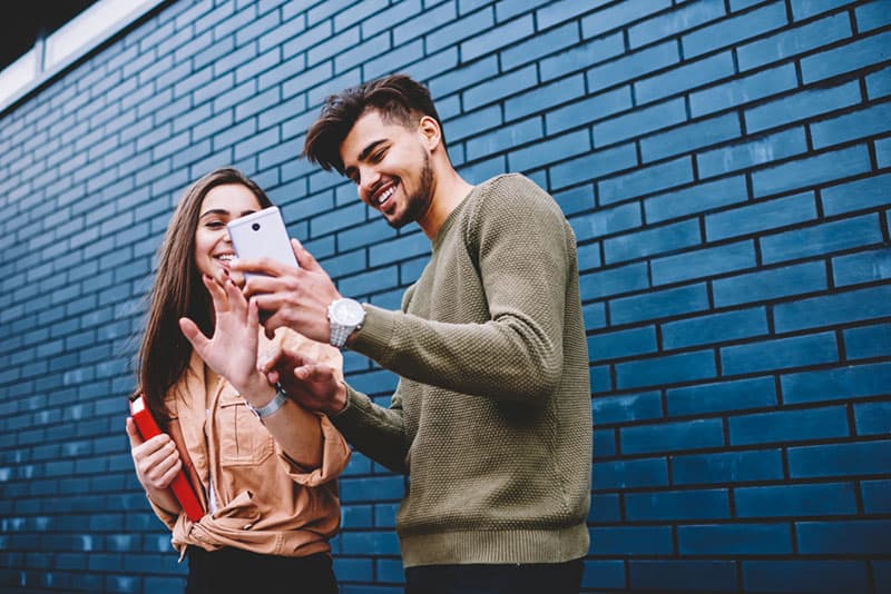 man showing phone to woman outside