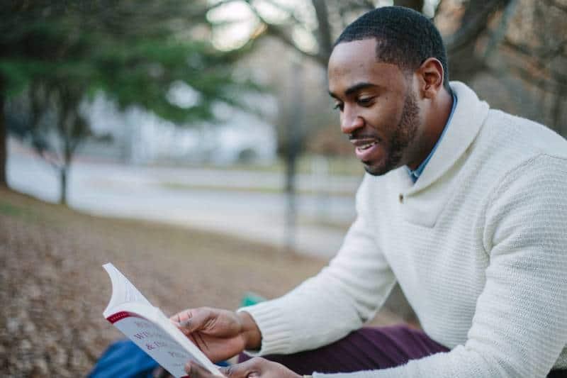 man wearing white sweatshirt while reading book