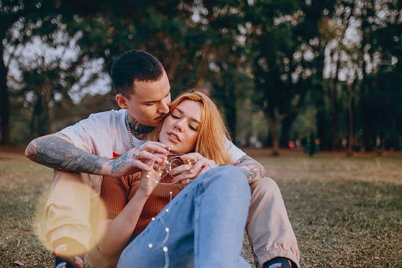 man with tattoo hugs woman from back while sitting on grass field