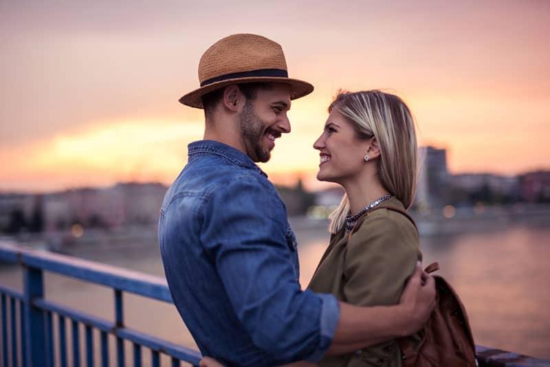 romantic couple standing on the bridge