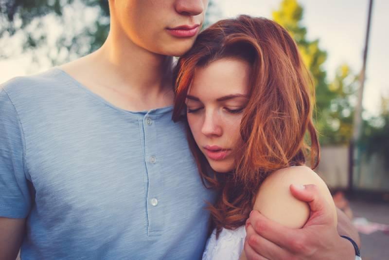 sad woman hugging her boyfriend outside