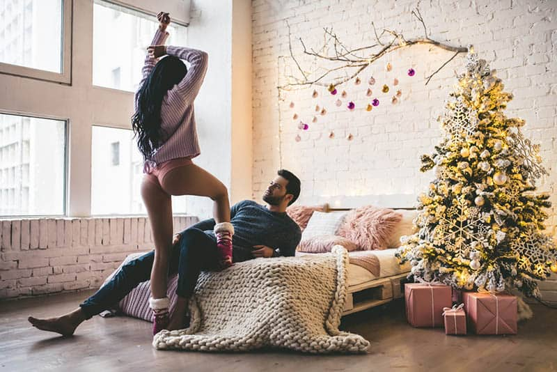 sexy woman playing with man in the living room