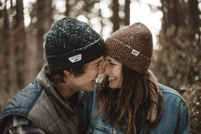 smiling couple looking each other during winter