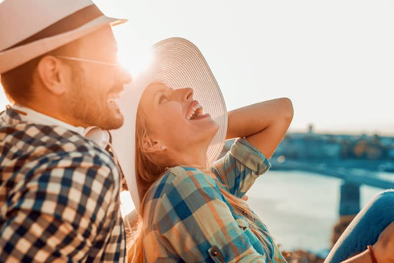 smiling couple with hat on sunset