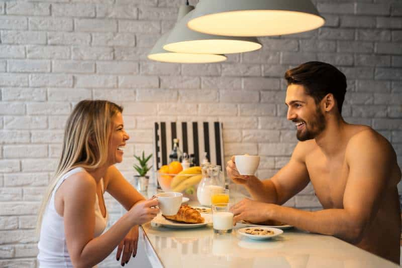 smiling man and woman talking while holding cup of coffee