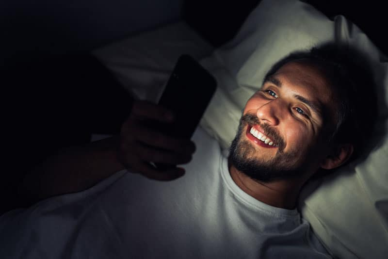 smiling man looking at his phone while lying on bed