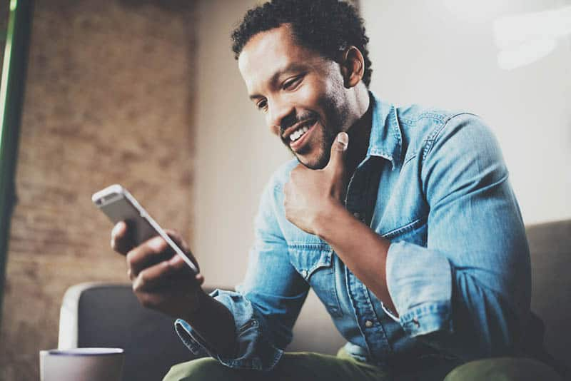smiling man sitting at couch and looking phone