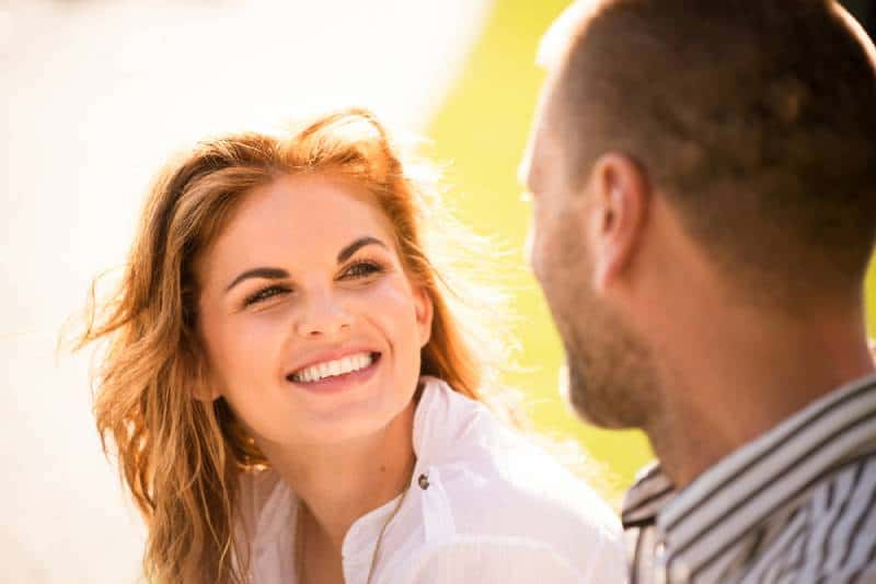smiling woman looking at man during daytime