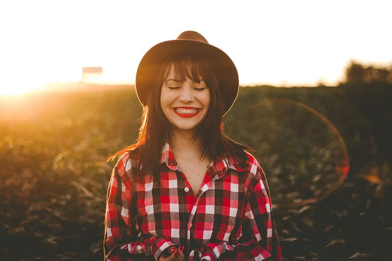 smiling woman with hat standing in the field