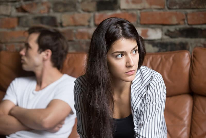 thoughtful woman sitting with her man at home