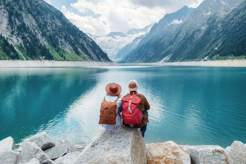 travel couple sitting in nature by the lake