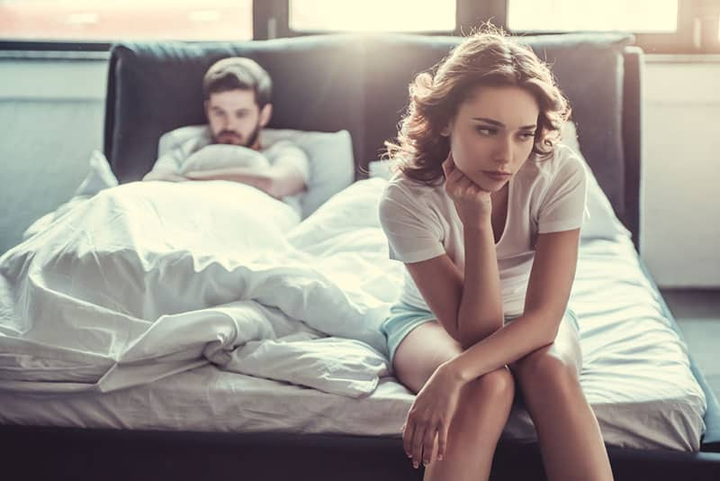 upset woman sitting on bed while man lying on bed