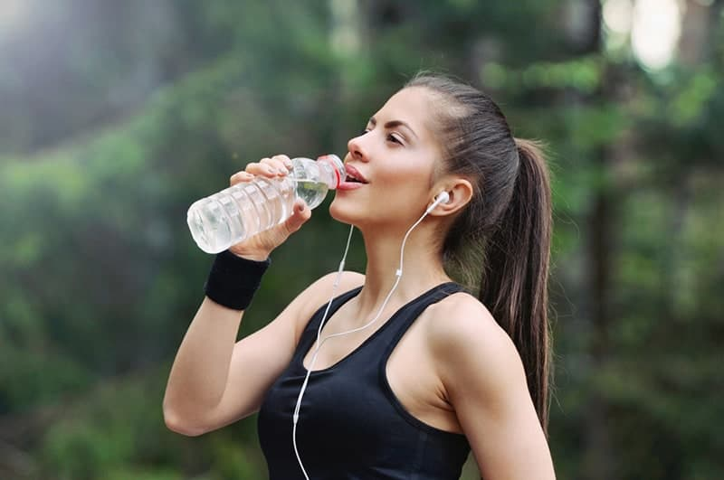 woman drinking water after running