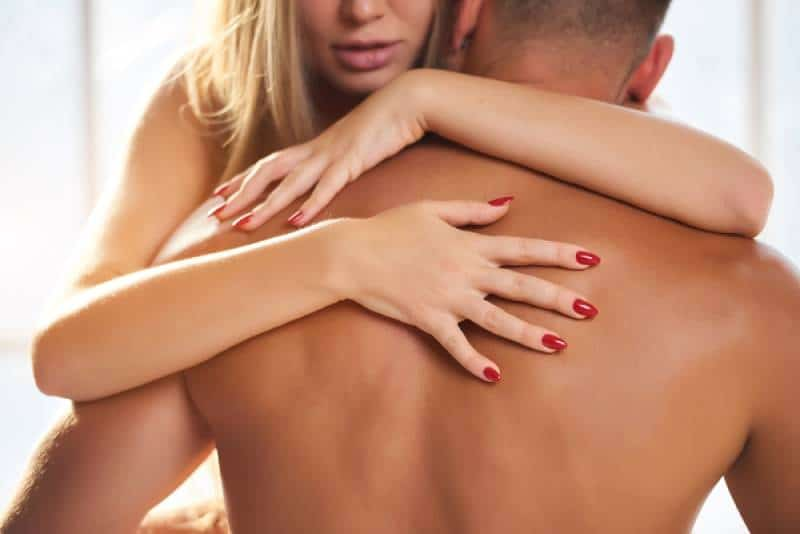 woman hands on male back