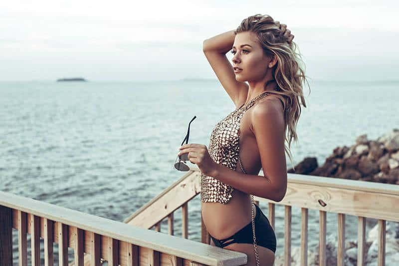 woman in bikini standing on balcony while looking at sea