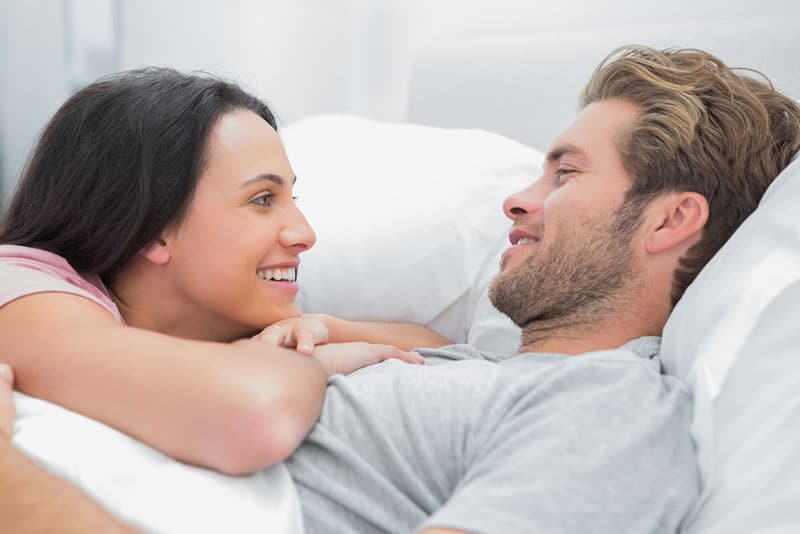 woman in love looking at her man in bed