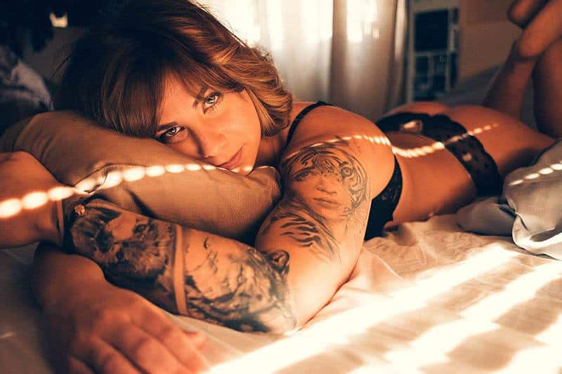 woman in underwear with arm tattoo lying on bed