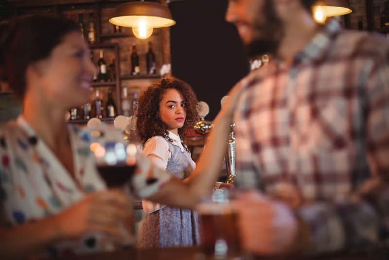 woman looking at couple at bar