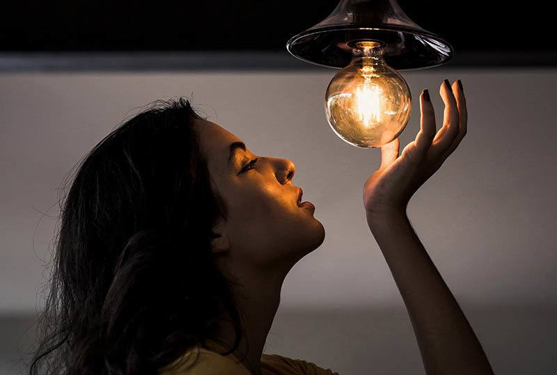 woman looking at light bulb