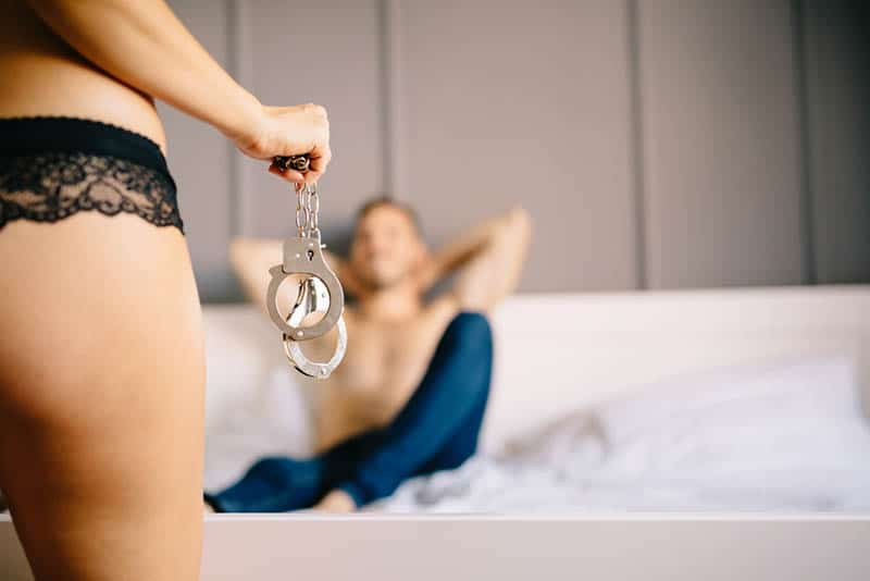 woman playing with man in bedroom